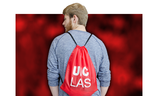 Young male student with his back to camera wearing UIC drawstring bag